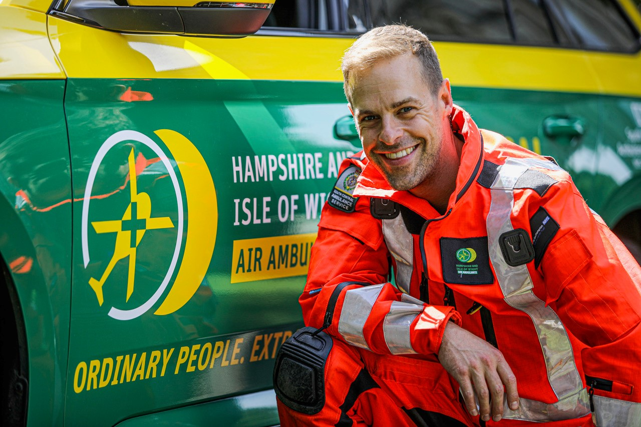 Dr Jamie Plumb is crouched in front of the HIOWAA emergency response vehicle and smiling to the camera. He is wearing the full flight suit.