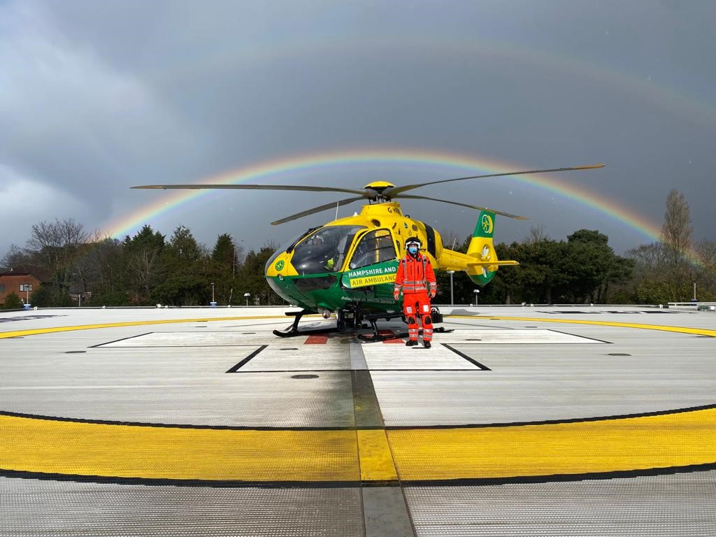 Crew standing on the helipad with the helicopter, under a double rainbow