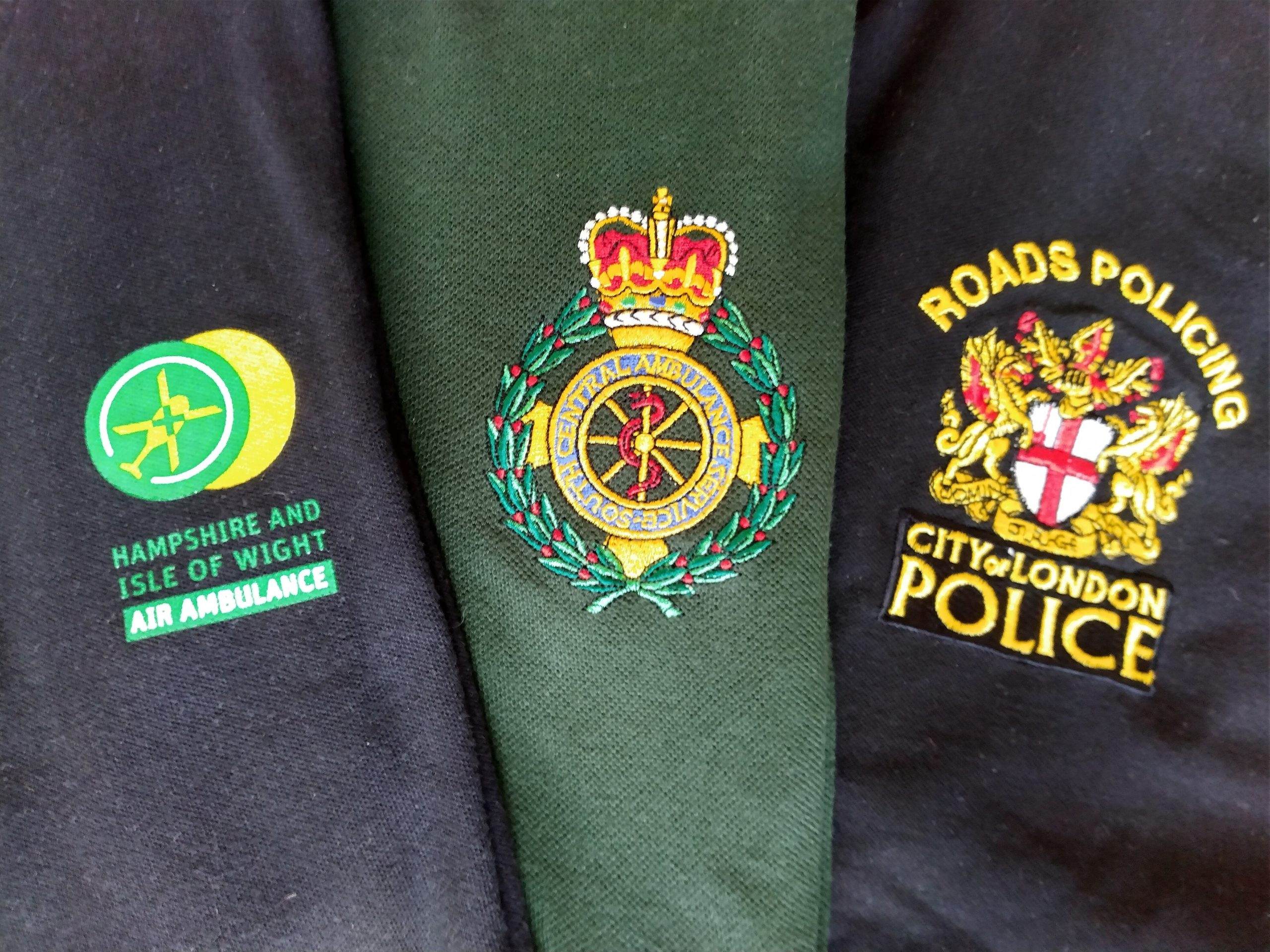 The top of the arms of three t-shirts. Each one has a logo on it. The first is the HIOWAA logo. Second is South Central Ambulance Service and the last is the logo for the London police.