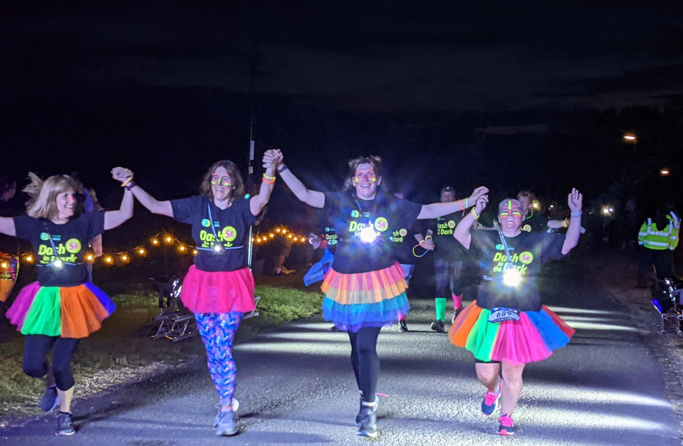 Dash in the Dark event - Four women dressed in florescent tutus and lights celebrate running across the finish line