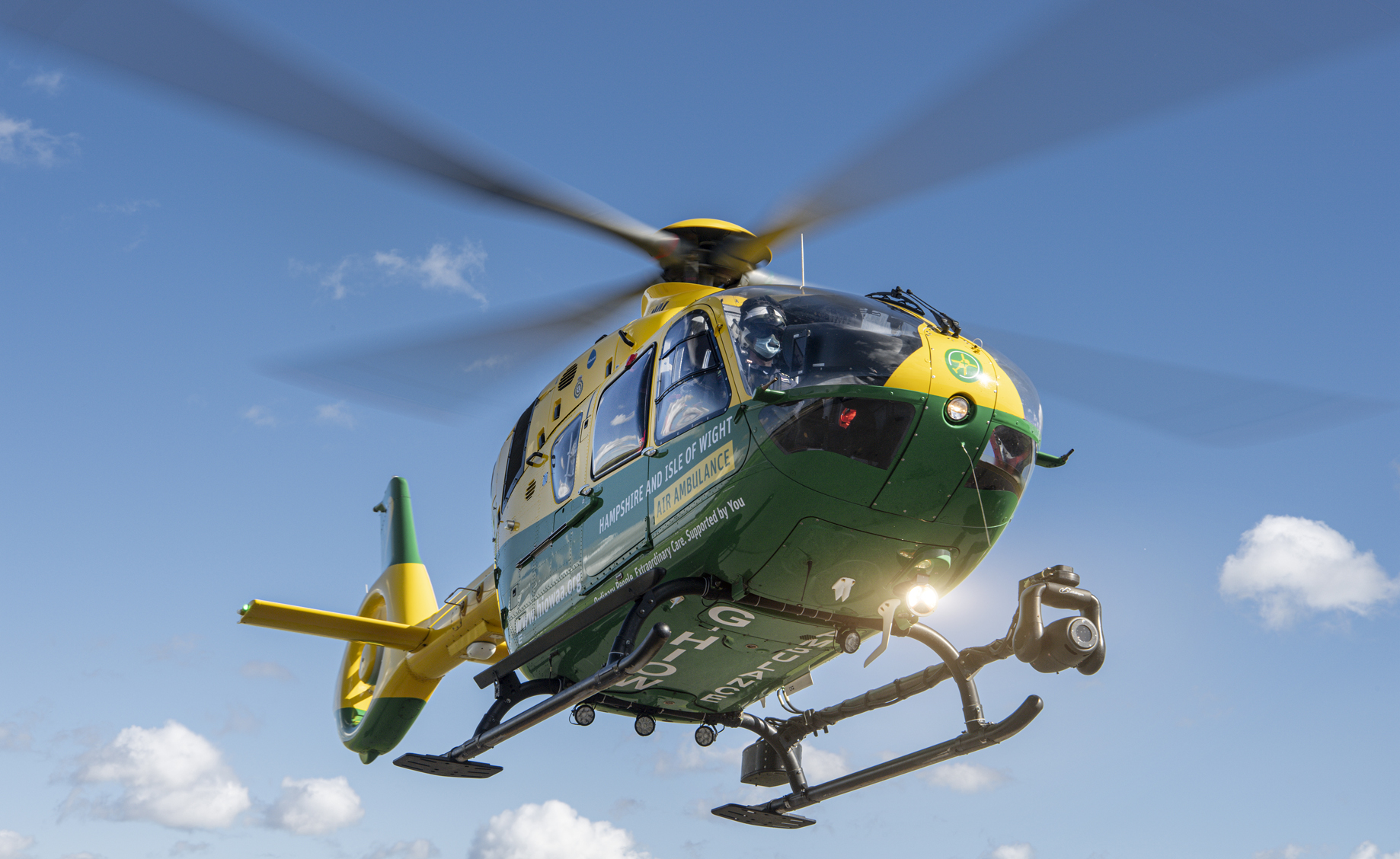 Our helicopter, Helimed 56, is in flight. The sky is blue and the search light underneath is on.