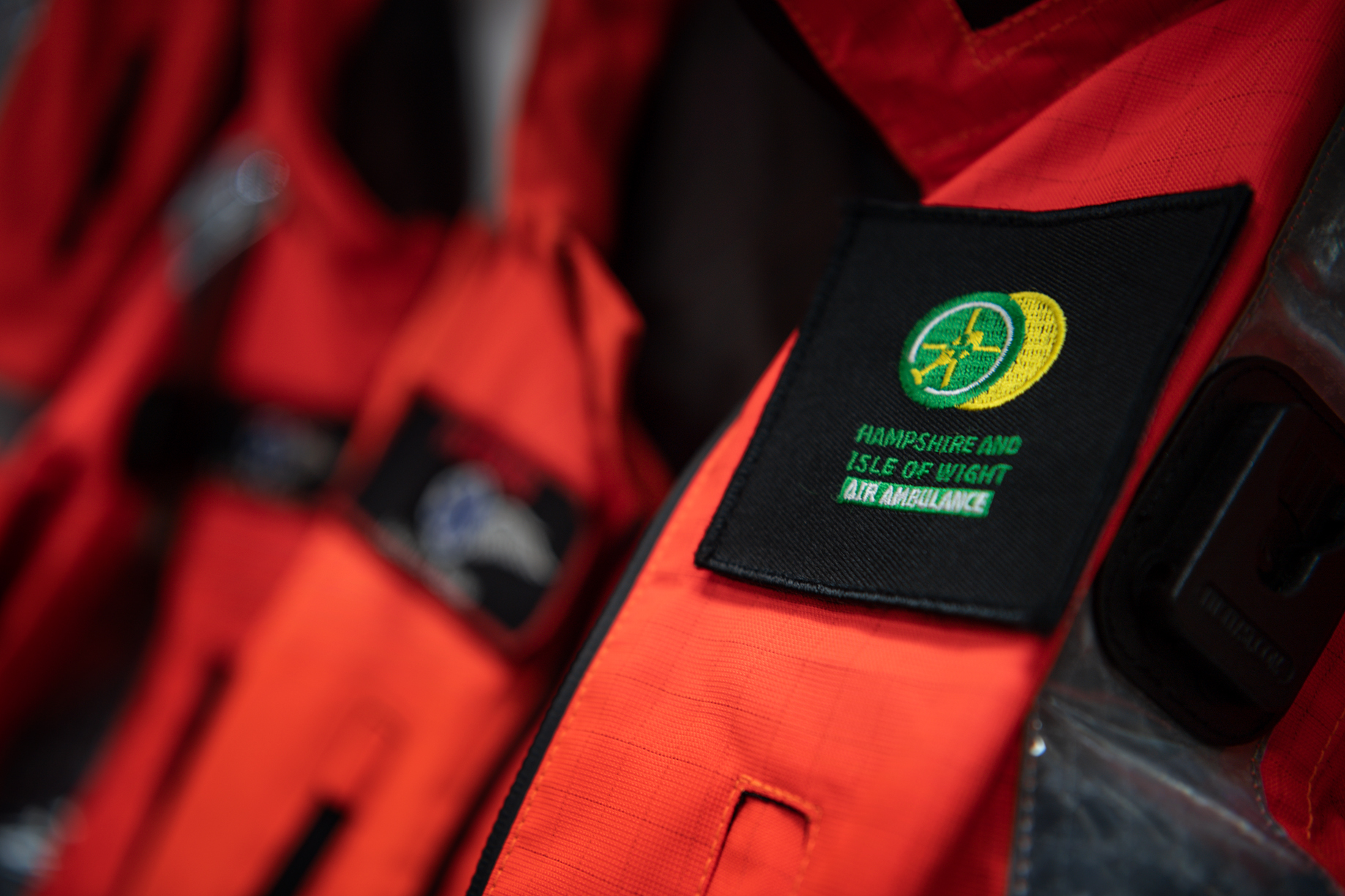 Crew flight suits are hanging on their pegs. The Hampshire and Isle of Wight Air Ambulance logo is in view.