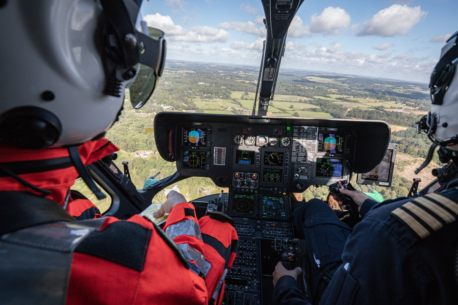 View from the inside of the helicopter looking out of the front. There is a paramedic to the left and the pilot to the right. We are flying over fields.