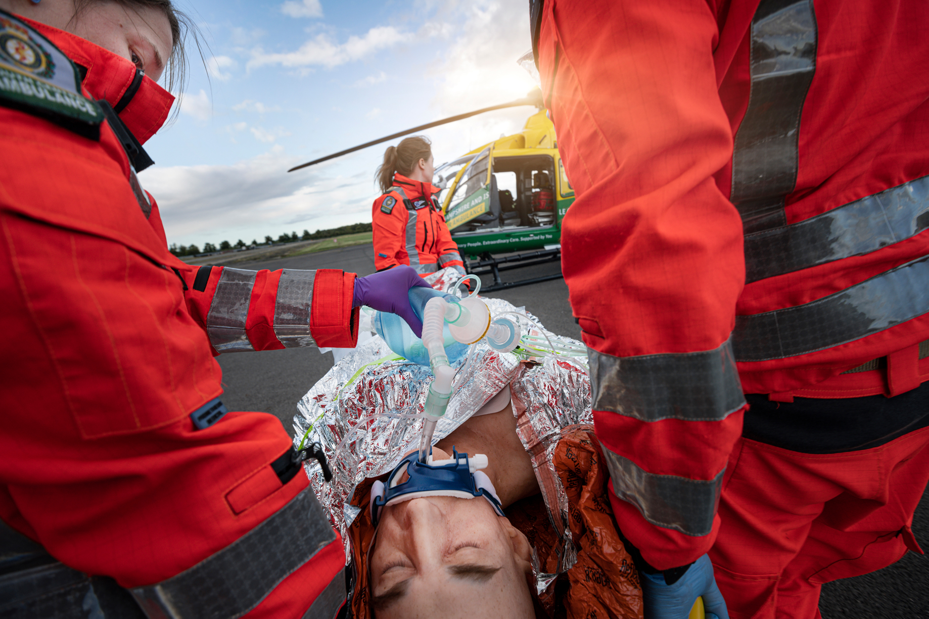 Three crew members are participating in a training simulation with a life like manikin. The manikin is on already packed onto a stretcher and is wearing an oxygen mask. The helicopter is in the background.