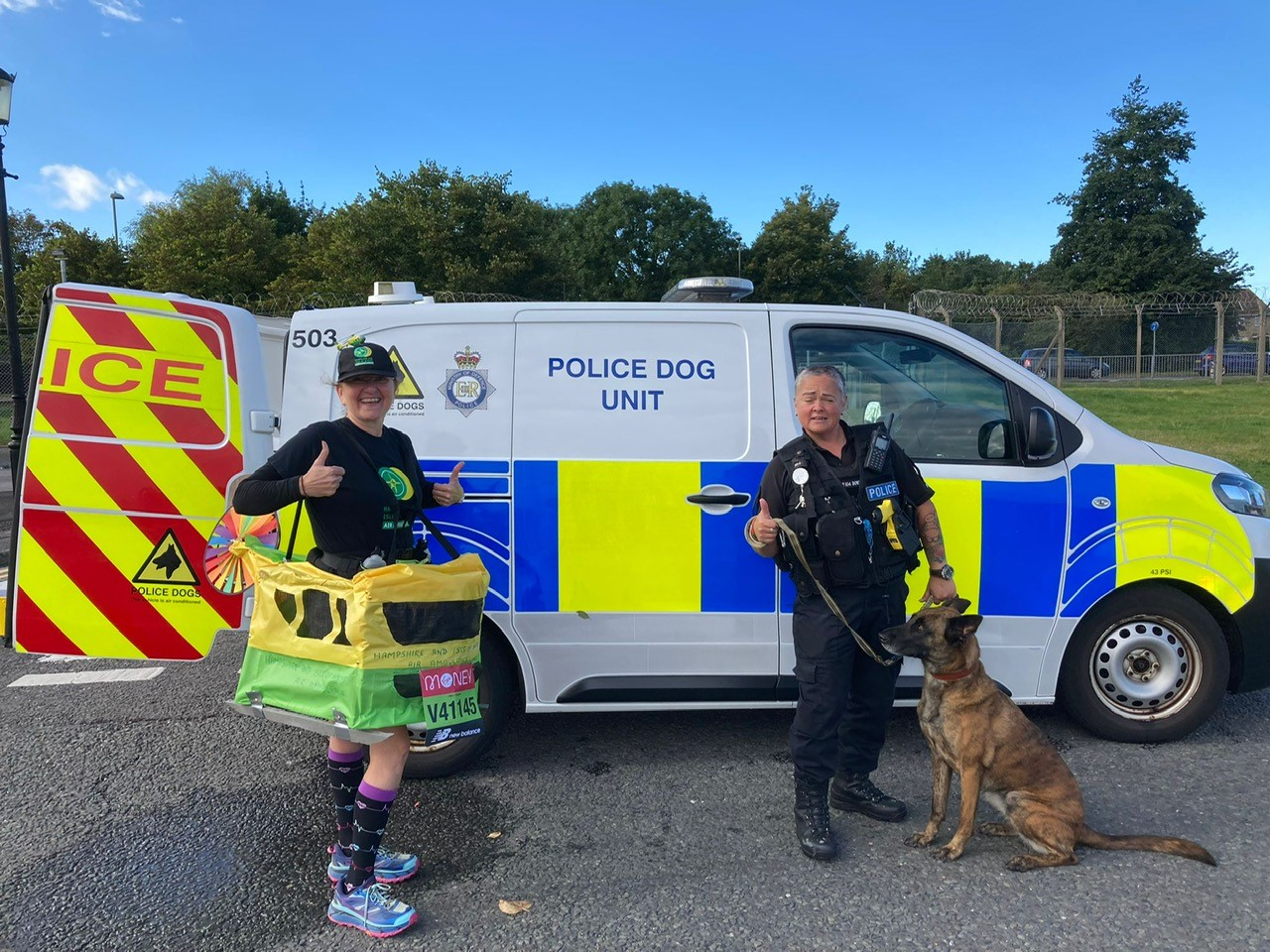 A runner standing in front of the Police Dog Unit van with a police officer and police dog