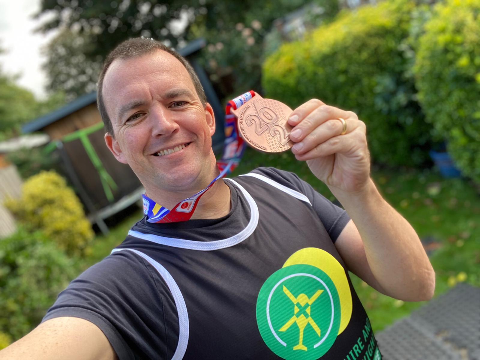 Ed Danson holding his London Marathon medal wearing a HIOWAA running vest